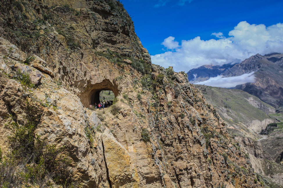 A crowd walks through a tunnel carved into the mountain in Colca Canyon, Peru.